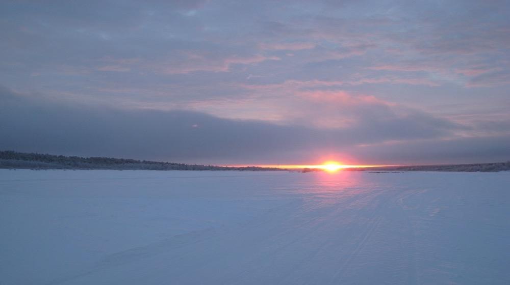 Happy-Fox-Trip-Along-the-Ounasjoki-River-on-Snowmobile-pulled-Sled-sunset-at-ounasjoki-river
