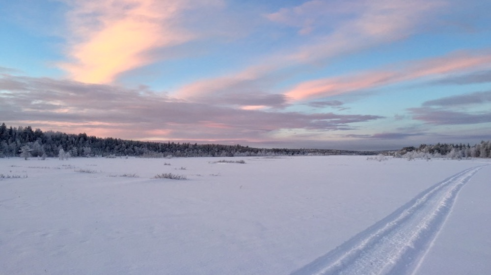 Happy-Fox-Trip-Along-the-Ounasjoki-River-on-Snowmobile-pulled-Sled-white-cloud-and-sled-track