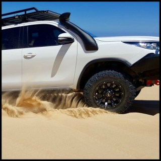Toyota Fortuner on beach with roof rack and snorkel