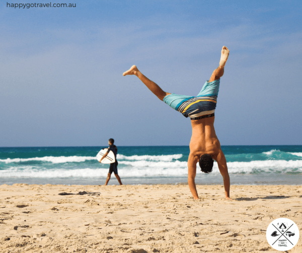 man exercising on beach - stay healthy while travelling