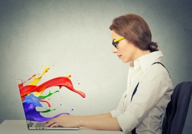 businesswoman working on a laptop with colorful splashes coming out of the screen