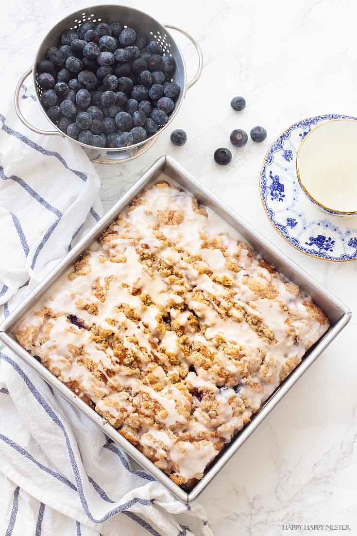 This New England dessert is The Best Blueberry Buckle Cake Recipe and is sure the perfect side to a cup of coffee or tea. Serve it as a dessert or as a morning blueberry coffee cake. This easy recipe makes an impressive cake with the crumble and delicious icing. #cake #coffeecake #blueberrydessserts #blueberries #desserts #pastry