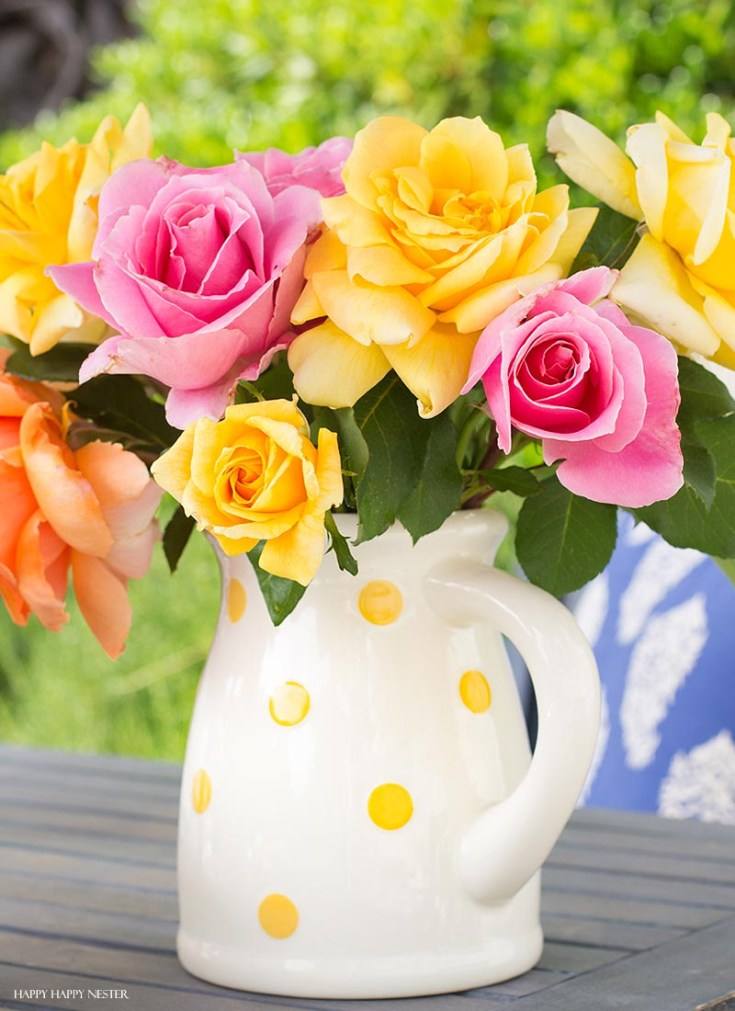 pink and yellow roses in a white pitcher