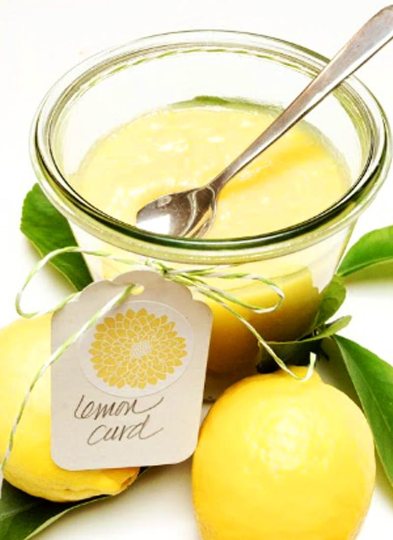 English Lemon Curd in glass container with lemons surrounding it