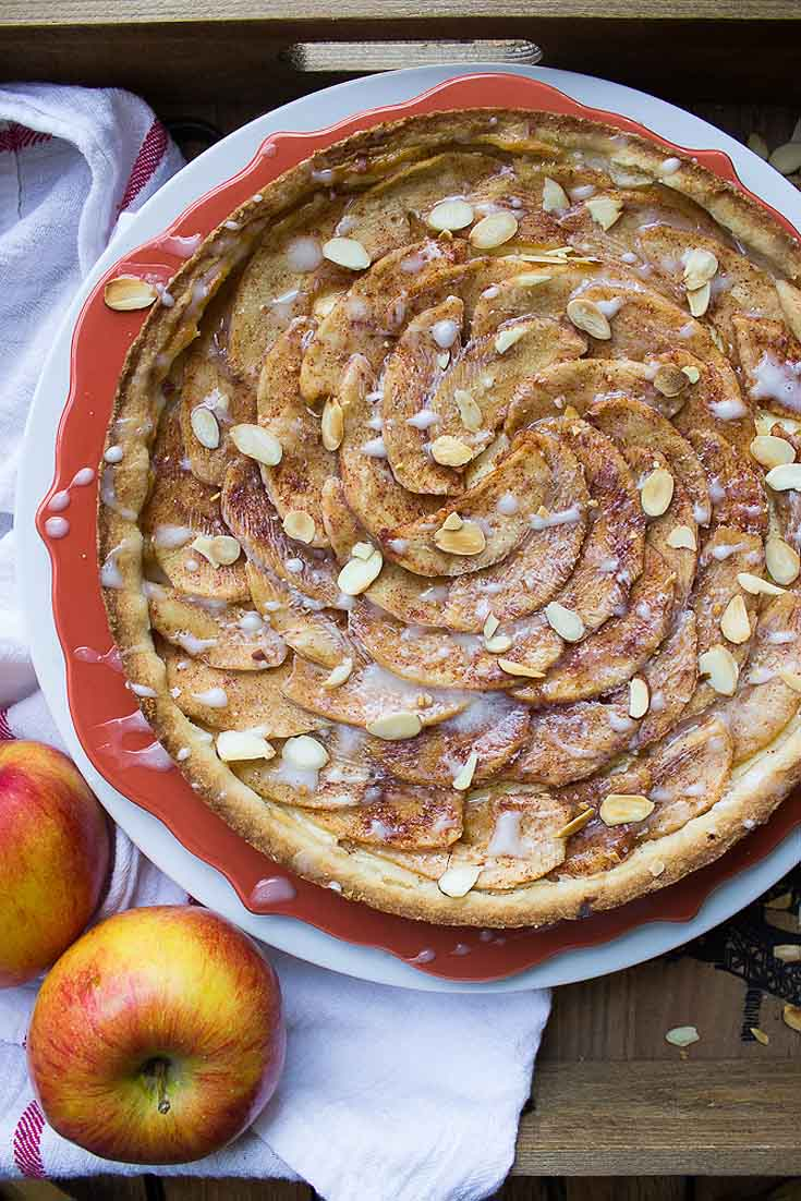 apple tart with almonds sprinkled on it. The tart is baked in a red pan