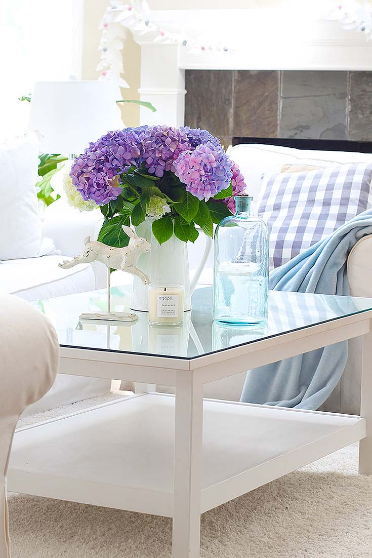 white living room decor with purple hydrangeas on a coffee table