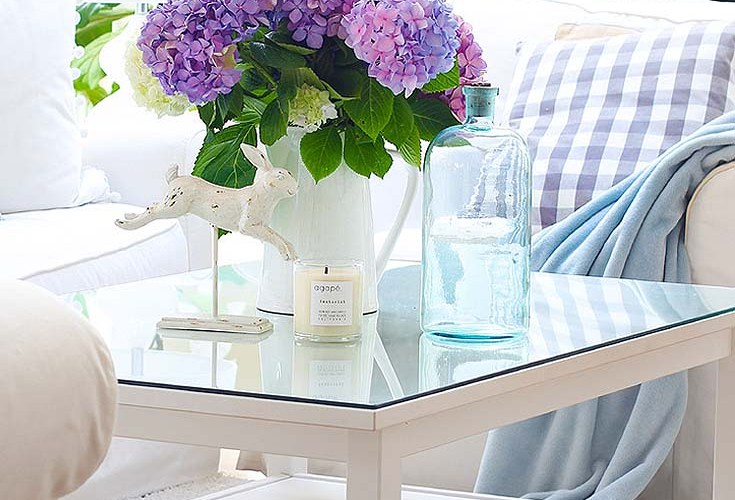 white living room with purple hydrangeas on a coffee table