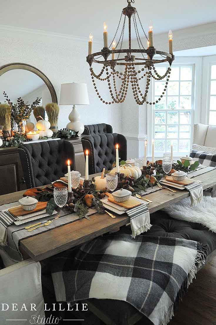 a fall table with black chairs and green and gold leaves