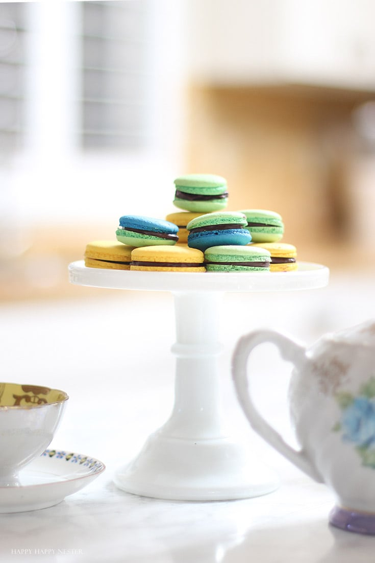 green and yellow macaron cookies on a white cake stand