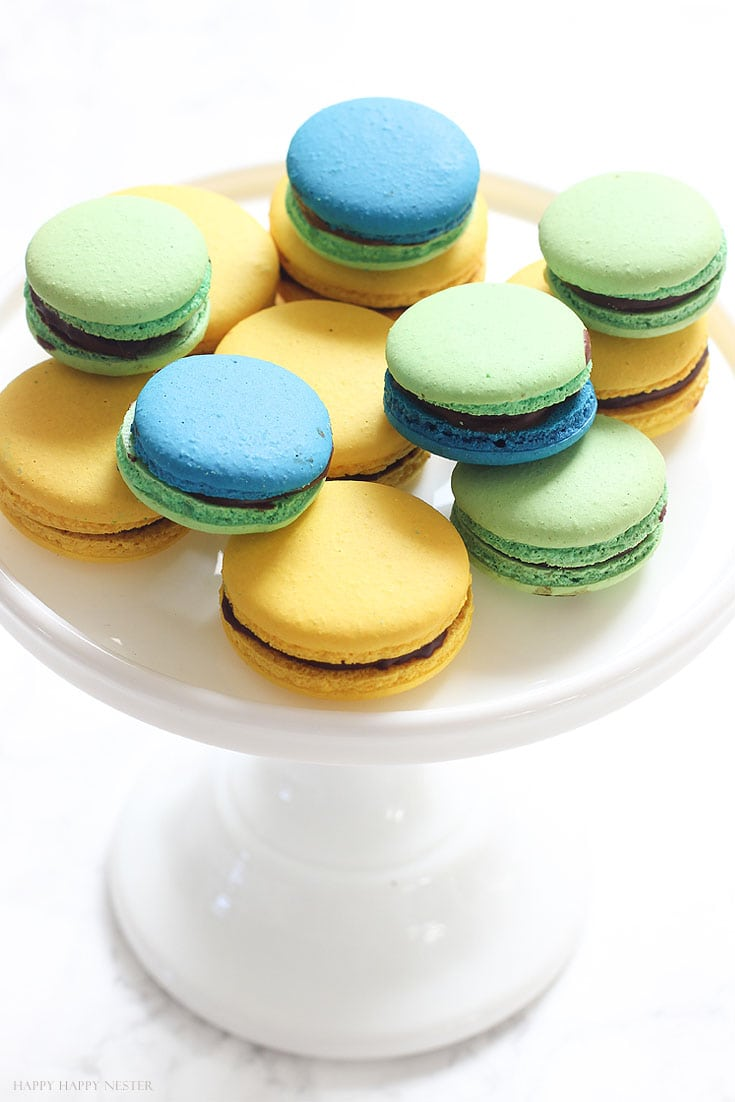 green, yellow and blue macarons on a white cake stand