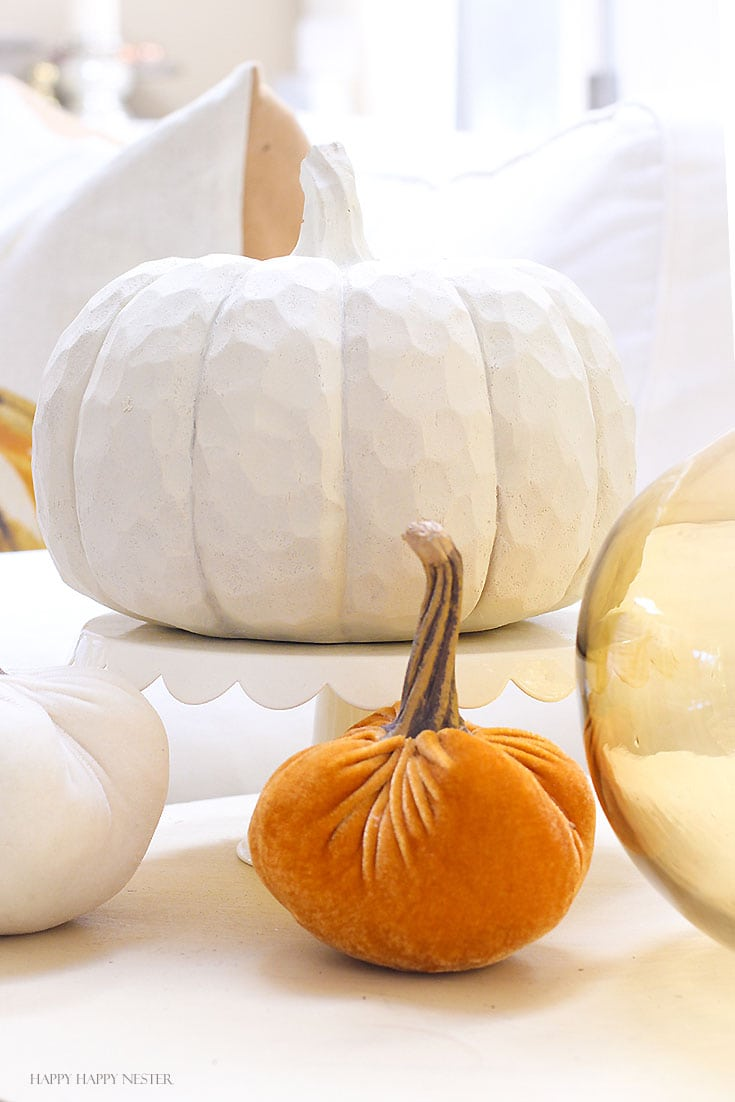 white pumpkin with two smaller pumpkins on a table