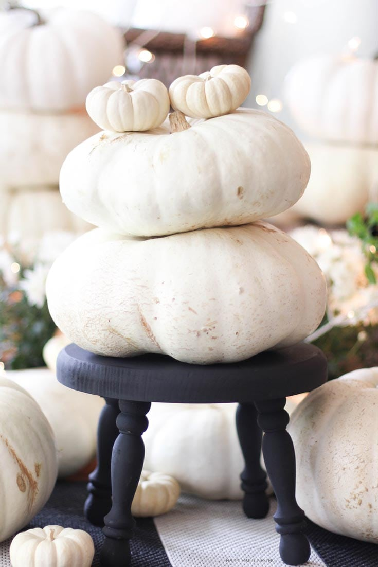 two white pumpkins stacked on top of each other on a black footstool