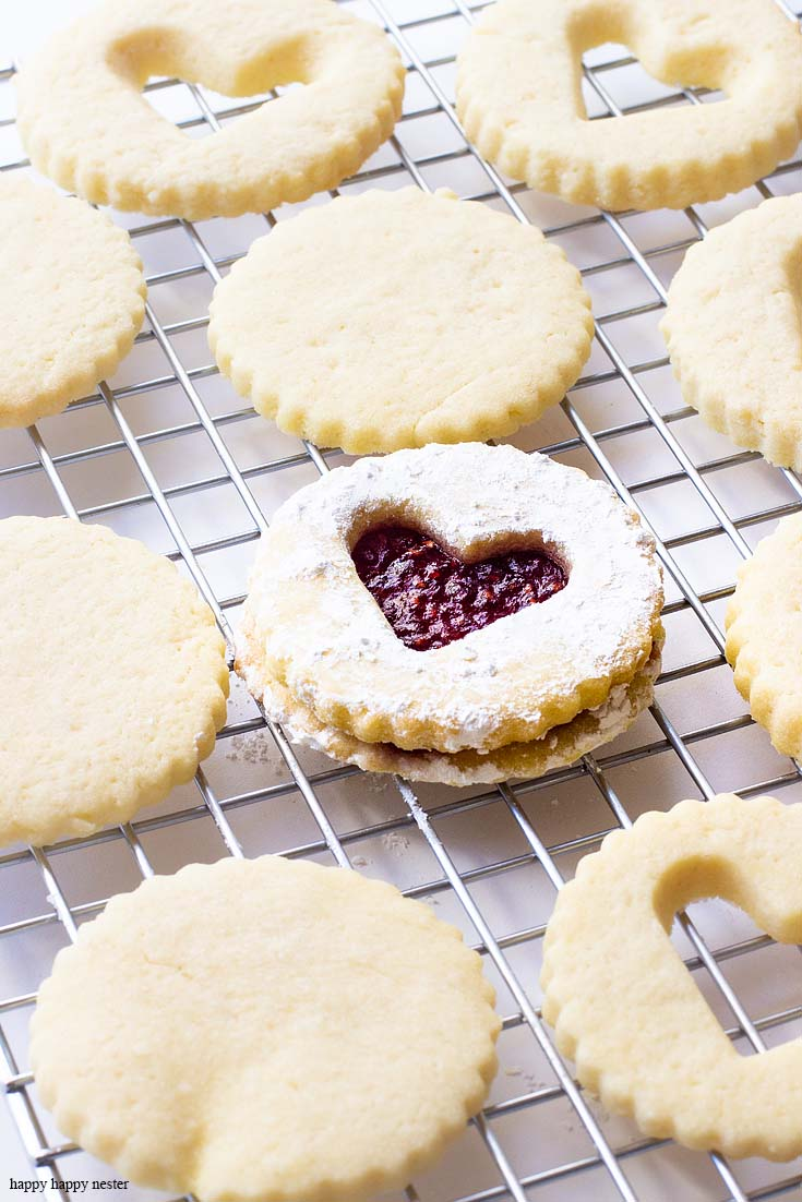 This raspberry filled valentine's heart cookie is the perfect dessert for a dinner or a party. Give them away as a Valentine's Day gift for a friend. Sprinkle them with powdered sugar for an extra-amazing sugar cookie. Cookie | Baking | Valentine's Day Treats | Cookie Recipe | Raspberry Filled Cookies