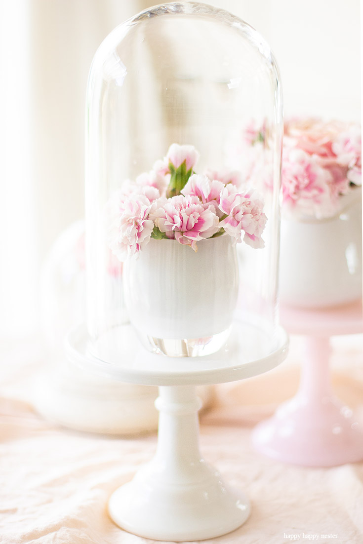 Add glass cloches on cake stands. Cake stands are easy ways to decorate a table or your home. I have gathered some Cute Ways to Use a Cake Stand that I'm sure you'll love. You can use them for the holidays or even a wedding reception. They add drama and interest because of their styles and heights. #cakestands #decorating #weddings #flowers #decor