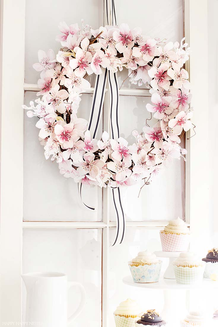 This easy How to Make a Paper Flower Wreath DIY is perfect for the spring. This wreath uses watercolor cherry blossoms that you cut out and glue to a grapevine wreath. It is a simple wreath that is beautiful and nice year round. The supplies include a wreath, paper, scissors, glue, and ribbon. #crafts #wreaths #spring