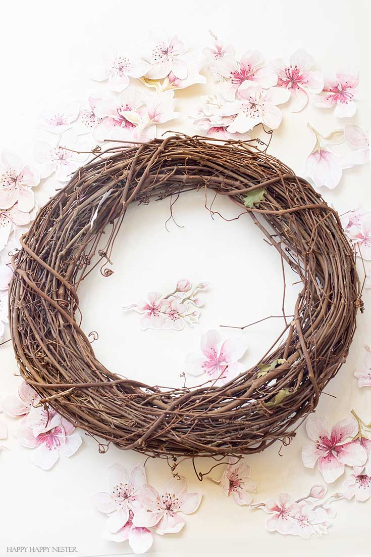 Love this grapevine wreath DIY. This easy How to Make a Paper Flower Wreath DIY is perfect for the spring. This wreath uses watercolor cherry blossoms that you cut out and glue to a grapevine wreath. It is a simple wreath that is beautiful and nice year round. The supplies include a wreath, paper, scissors, glue, and ribbon. #crafts #wreaths #spring