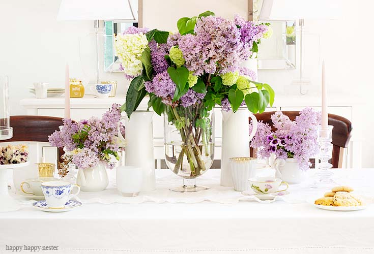 Here is an easy way to decorate your spring table. It doesn't take much to create a Beautiful Spring Table with Fresh Flowers. This spring table with fresh lilacs and other garden flowers is so easy to create. No need to spend much to style a fabulous spring table. #springtable #flowerbouquet #freshflowers #lilacs #lavendertable #decoratingwithlilacs #purplelilacs