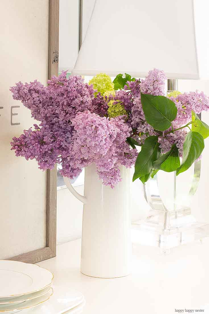 Placing lilacs in vases is the best way to decorate your home. It doesn't take much to create a Beautiful Spring Table with Fresh Flowers. This spring table with fresh lilacs and other garden flowers is so easy to create. No need to spend much to style a fabulous spring table. #springtable #flowerbouquet #freshflowers #lilacs #lavendertable #decoratingwithlilacs #purplelilacs