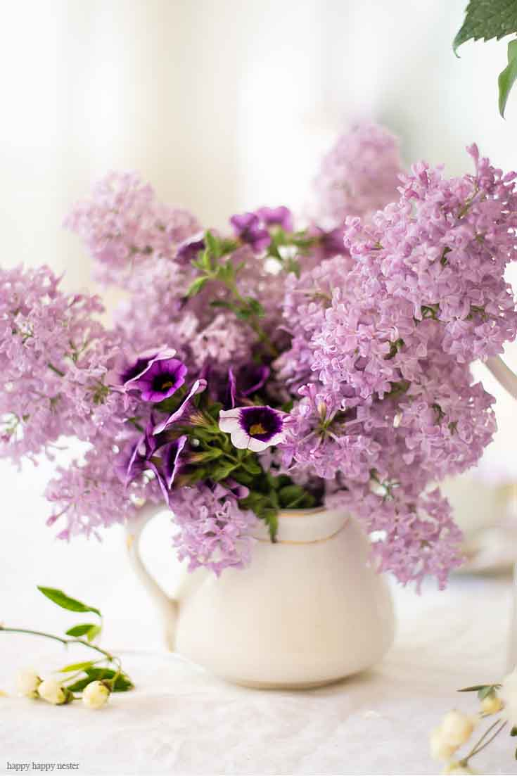 It doesn't take much to create a Beautiful Spring Table with Fresh Flowers. This spring table with fresh lilacs and other garden flowers is so easy to create. No need to spend much to style a fabulous spring table. #springtable #flowerbouquet #freshflowers #lilacs #lavendertable #decoratingwithlilacs #purplelilacs