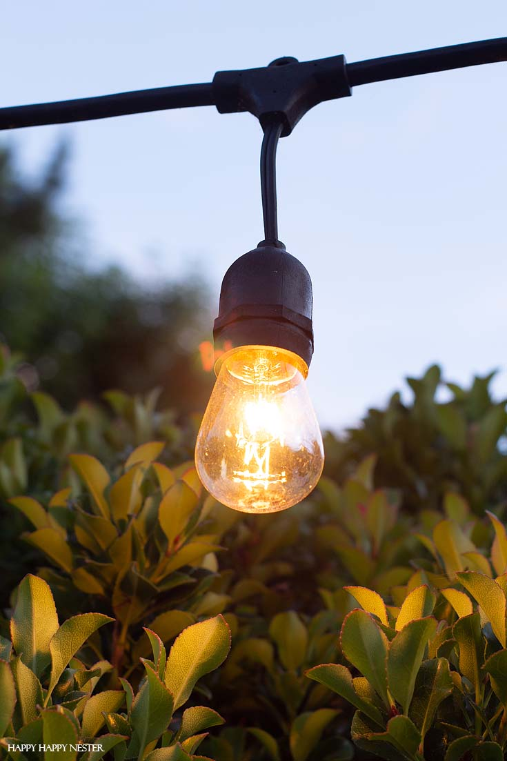 Learn how to Hang Outdoor String LIghts in cement supports. This technique is a solid solution and these light poles are easy to install and are stable.#DIY #outdoorlights #patios #gardenprojects