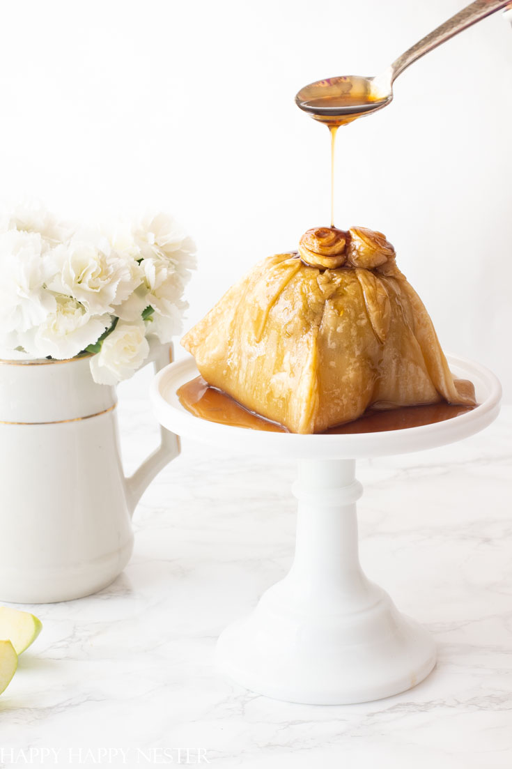 This apple recipe is simply amazing! The apple has sugared nuts inside and is topped with a pastry dough and caramel sauce. #dessert #appledumpling #appledesserts