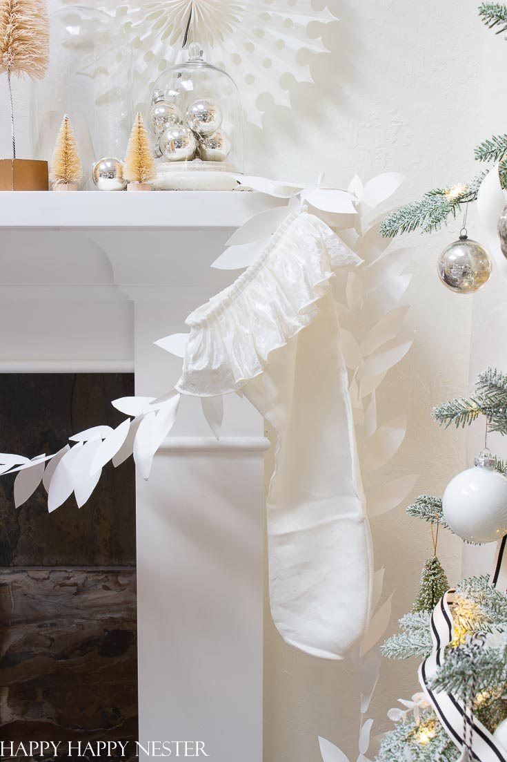 Here is a bright and merry Christmas mantel. The white holiday decor includes two garlands, felt fleece trees, and vintage ornaments. Head on over to see 41 mantels from some very talented bloggers. #christmasmantel #decorateforchristmas #christmasdecor #holidaydecorating