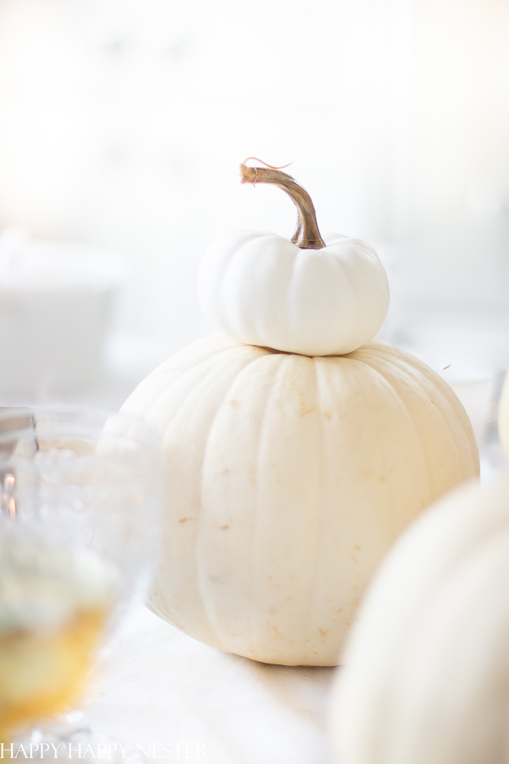 Here is a Thanksgiving Table Setting Made Easy. Find out how the 7 elements to set a Thanksgiving table step by step. White pumpkins are a must when creating a table setting. This table has all-natural elements and wheat makes a beautiful fall centerpiece for a table. #thanksgiving #thanksgivingtable #tabledecor #createathanksgivingtable #tablesetting