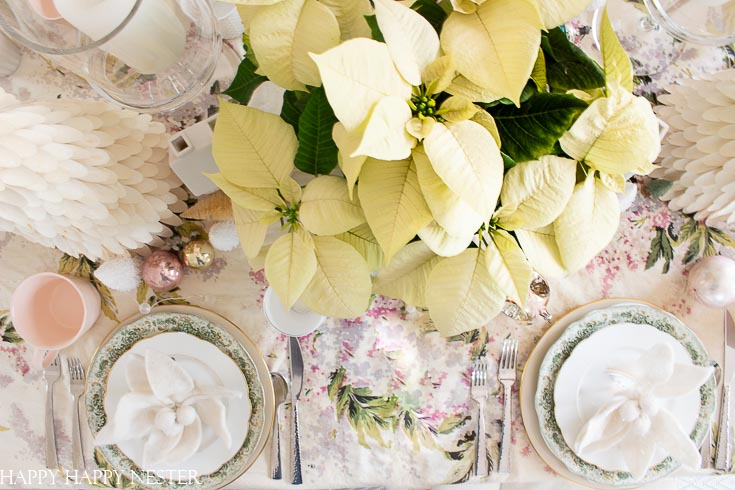 Use white Christmas poinsettias on your holiday tables. Also, when it comes to tablecloths, use vintage material for a romantic shabby chic cottage style. Find out these table ideas for Christmas decorating. This table decor is feminine and vintage all rolled up in one. #shabbychic #Christmasvintage #vintageornaments #whitepointsettias