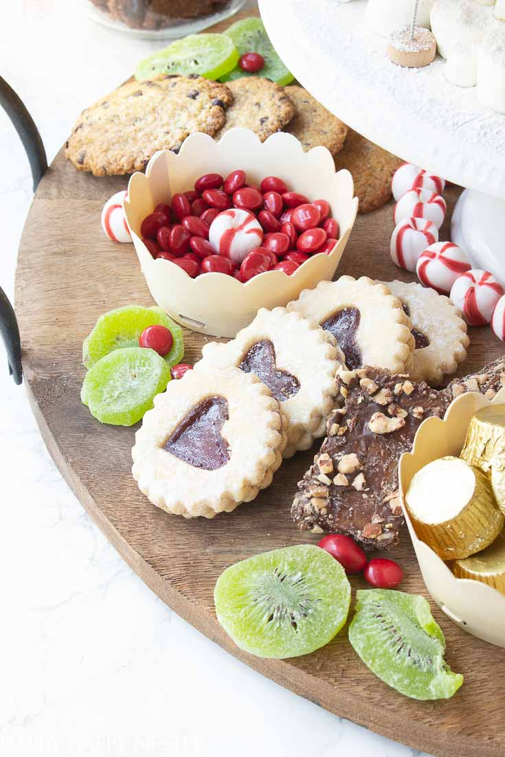 Add your favorite items to create this fun Christmas dessert board. This charcuterie includes my favorite chocolate chip, raspberry heart, and almond cookie recipes. #cookies #christmasdessert #christmascookies
