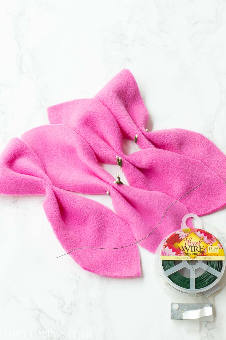 This step by step tutorial on how to make flowers out of fleece is perfect. Make this pretty fleece poinsettia to top a Christmas gift. #craft #fleececrafts #flowerdiy #christmasgift #wrappingideas