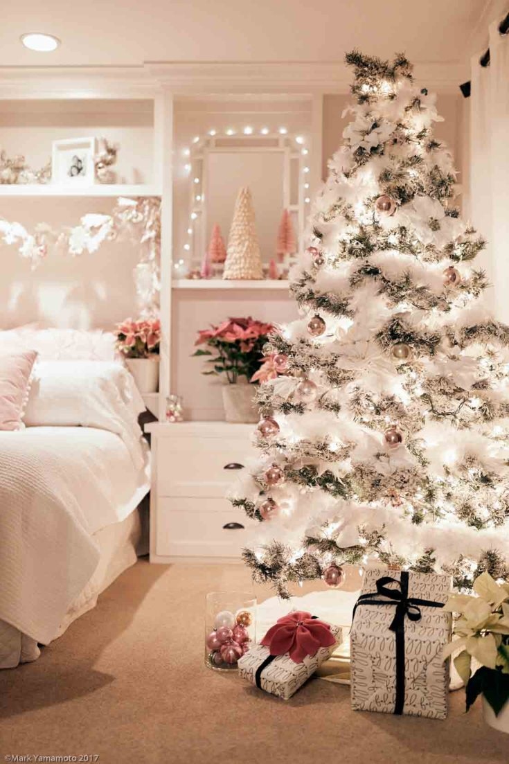 This pink Christmas decor is a winter wonderland. Pink poinsettias, bottle brush trees, and vintage pink ornaments are all the decor used in this holiday bedroom. It is festive, pretty, and feminine and perfect for the long winter nights. #christmas #holidaydecor #decorating