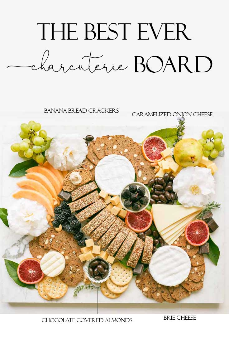 This impressive Charcuterie Board is elegantly styled with delicious cheeses, slices of bread, fruit, and chocolates. This epic appetizer will wow friends. #charcuterieboard
