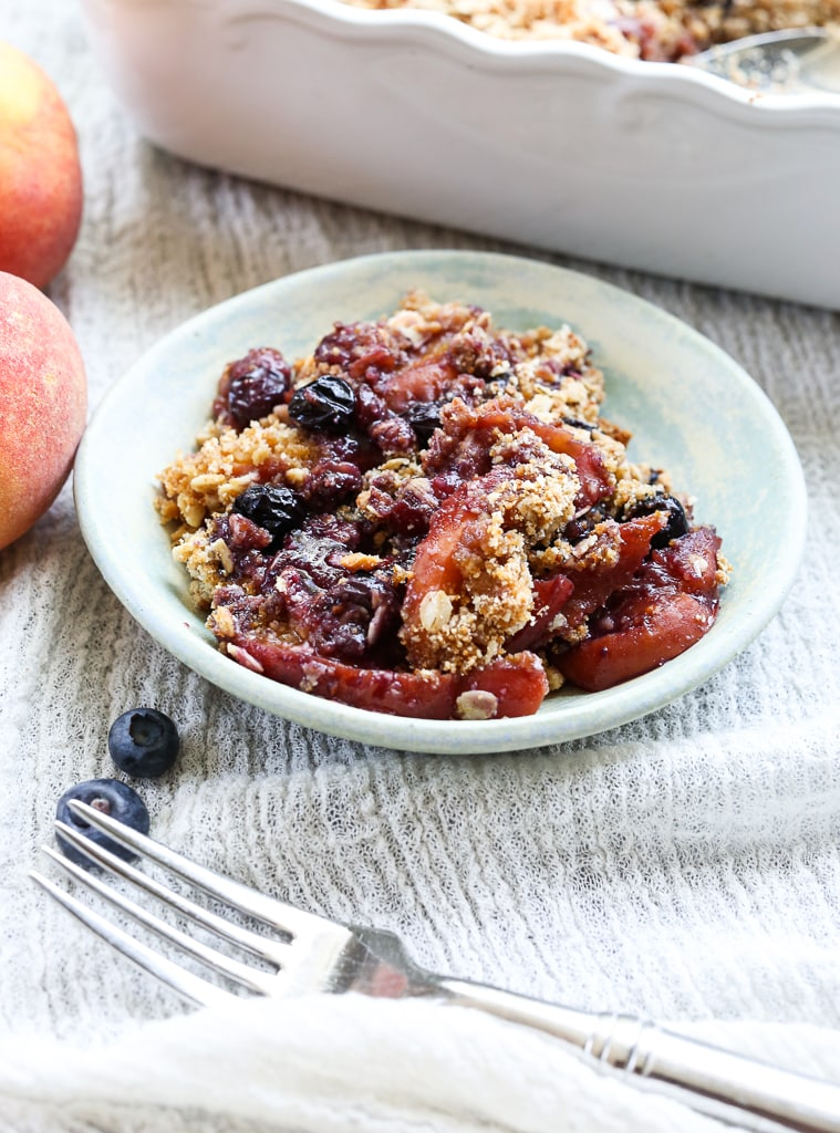 a close up shot of one serving of Peach Blueberry Crisp in a small dish