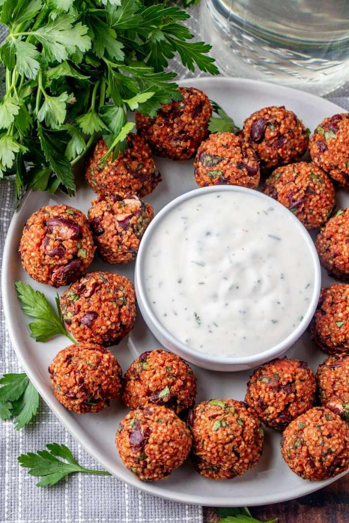 a plate of quinoa pizza balls with yogurt ranch dip in the middle