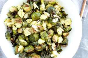 full shot of Roasted Brussels sprouts with apples and almonds in a white bowl recipe