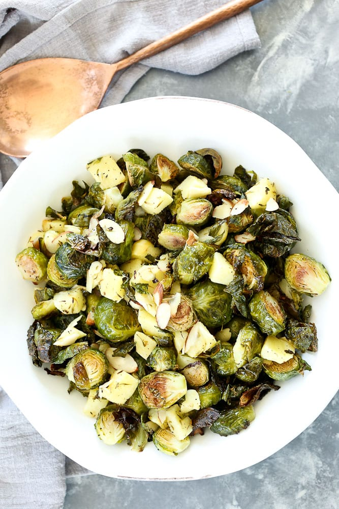 Roasted Brussels Sprouts with Apples and Almonds recipe with a copper serving spoon