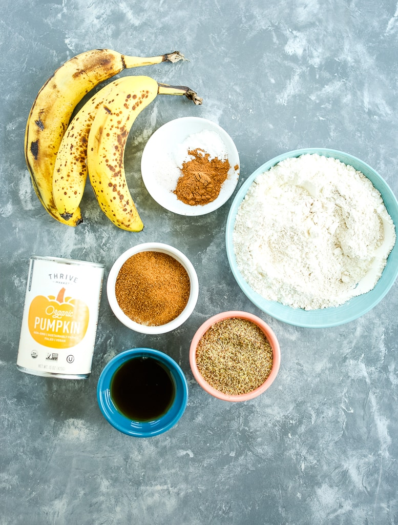 ingredients overhead shot: bananas, flour, sugar, maple syrup, pumpkin, spices flaxseed