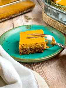 a pumpkin pie bar on a plate with a fork going in.