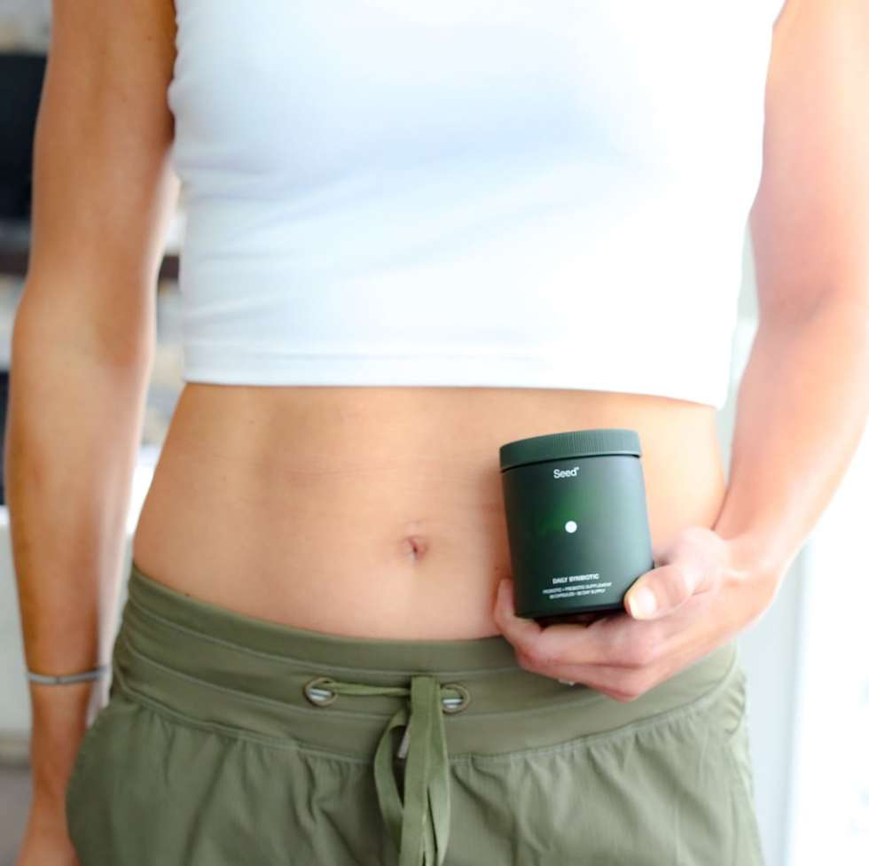 a woman with a bare stomach holding a bottle of supplements