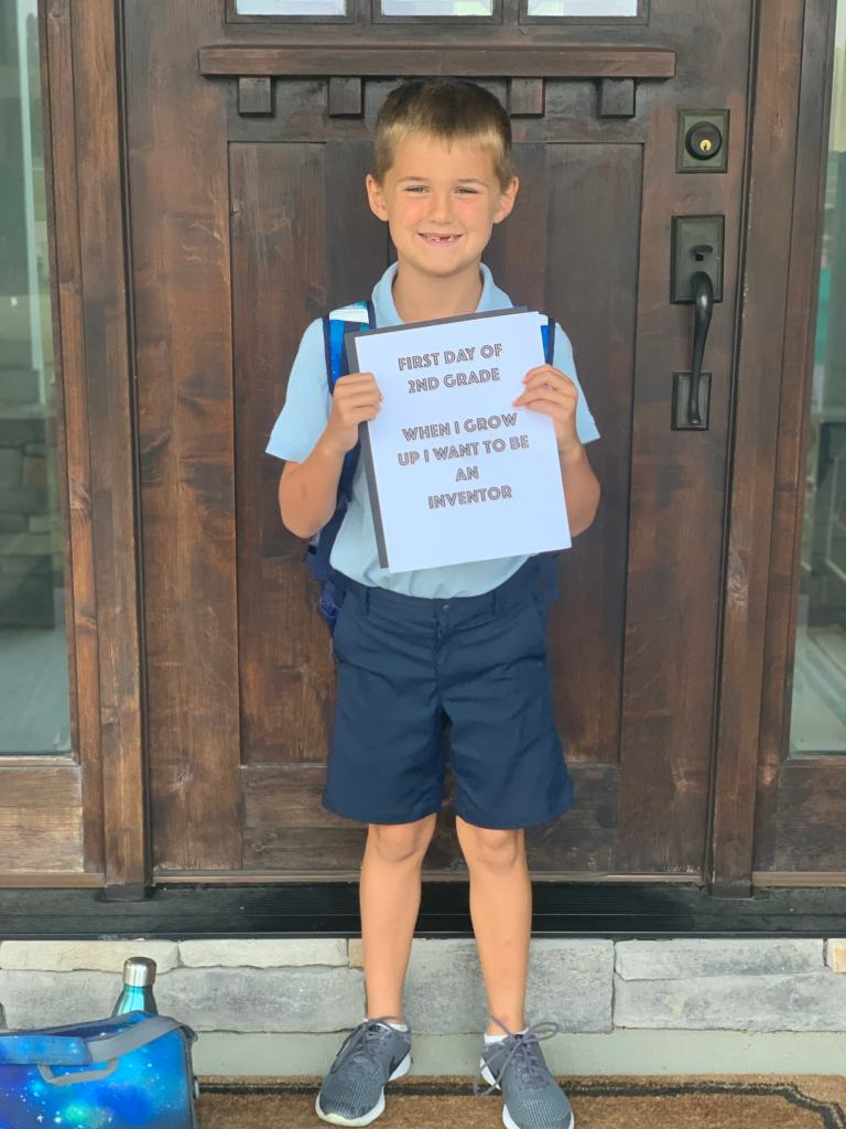 Luke Dawson holding a first day of school sign that says he wants to be an inventor
