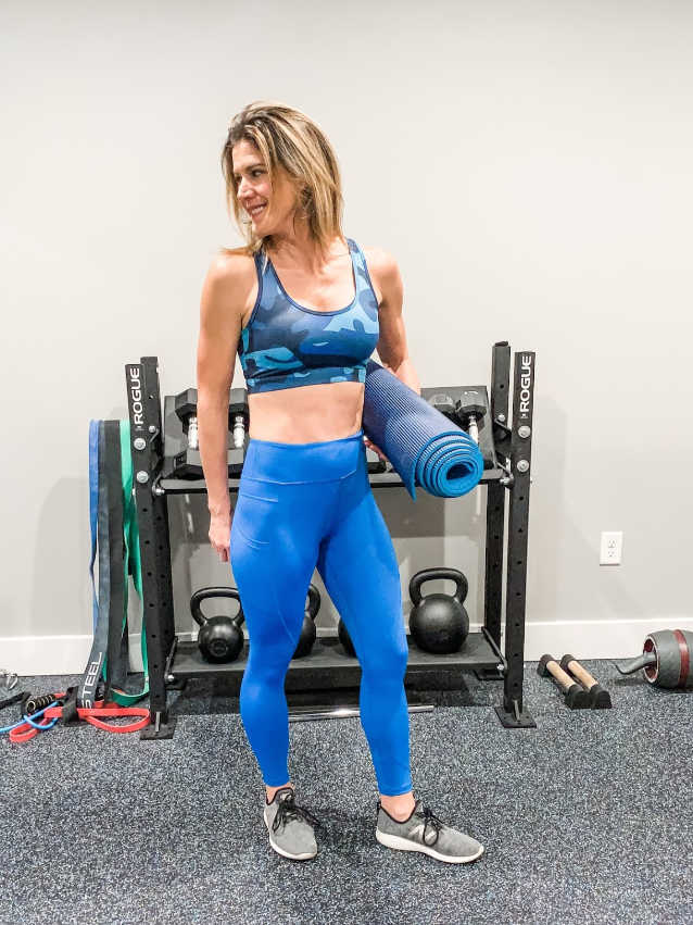 Maryea standing in a sports bra and leggings holding a yoga mat
