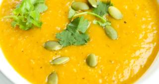 a close up picture of orange hued soup in a white bowl with parsley and pumpkin seeds on top