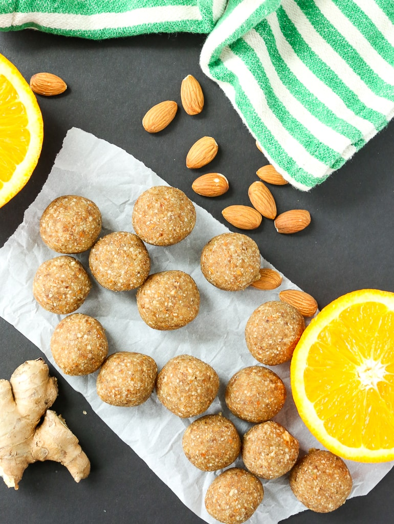Anti-inflammatory Ginger Energy Balls overhead shot with a cut orange, almonds, fresh ginger, and a green and white striped napkin