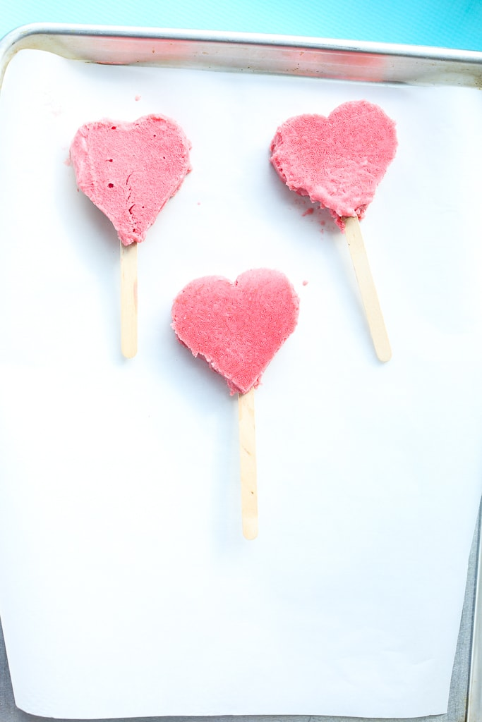 three heart-shaped strawberry bars with wooden sticks on a tray lined with white parchment paper