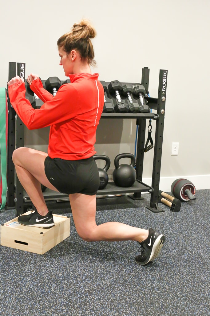 Maryea Flaherty in a red jacket and black shorts completing a reverse lunge exercise with one foot on a brown box