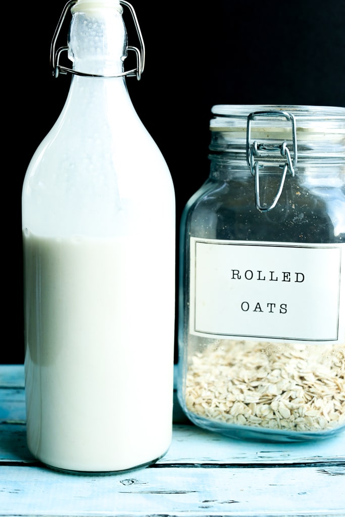 A bottle of oat milk with a jar of rolled oats in the background