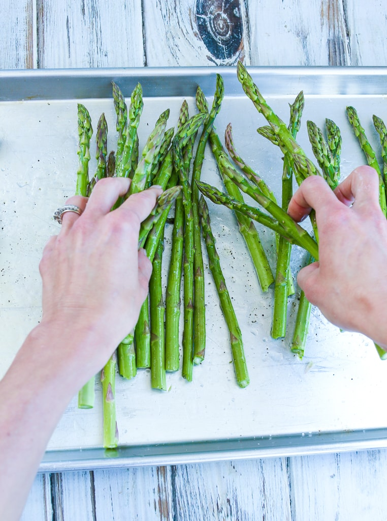 a tray of baked asparagus with melted parmesan cheese and lemon zest
