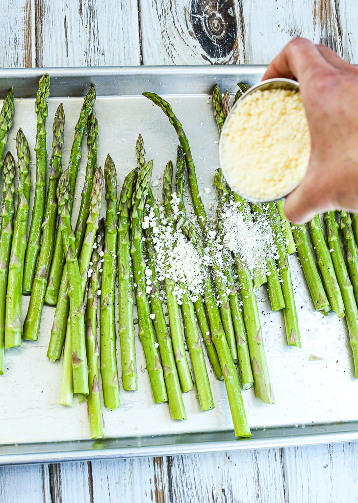 a cup of parmesan cheese being dumped on asparagus