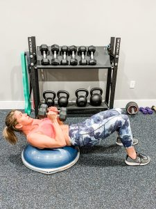 a woman in floral leggings and a sports bra laying on a bosu ball and arms near her chest with dumbbells