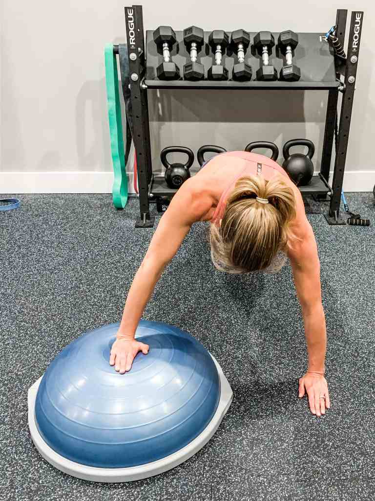 A woman completing a push up with one hand on a Bosu Ball